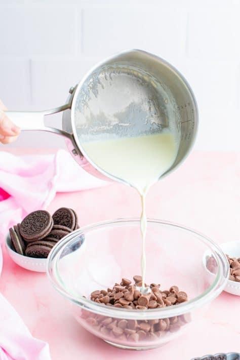Creme espesso sendo derramado sobre gotas de chocolate em uma tigela