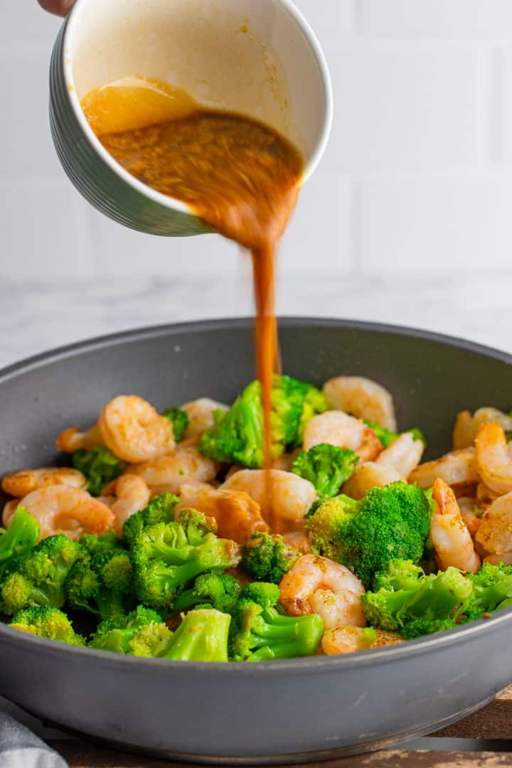 Sauce being poured over shrimp and broccoli in pan