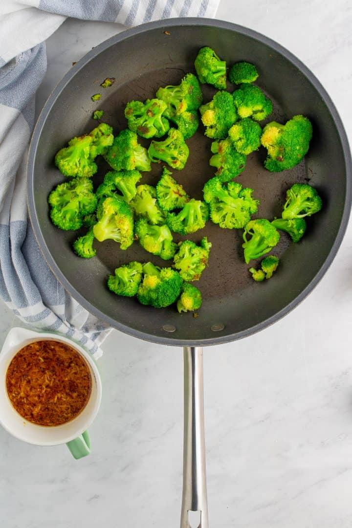 slightly browned broccoli florets in a skillet