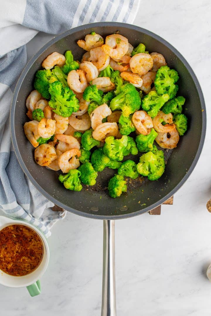partially cooked Broccoli and shrimp in a skillet
