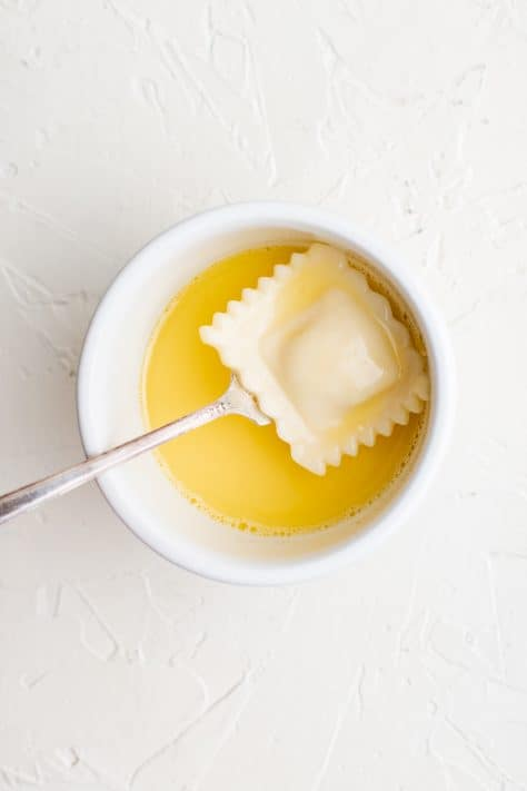 Eggs in bowl with ravioli being coated