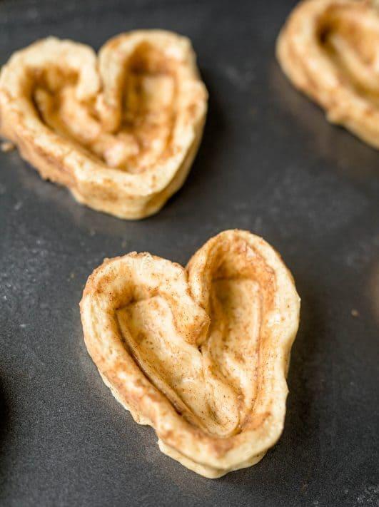 Cinnamon rolls shaped like hearts on baking sheet