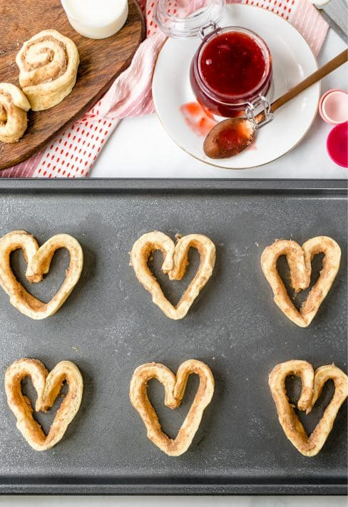 cinnamon roll dough shown shaped into hearts and on a cookie sheet