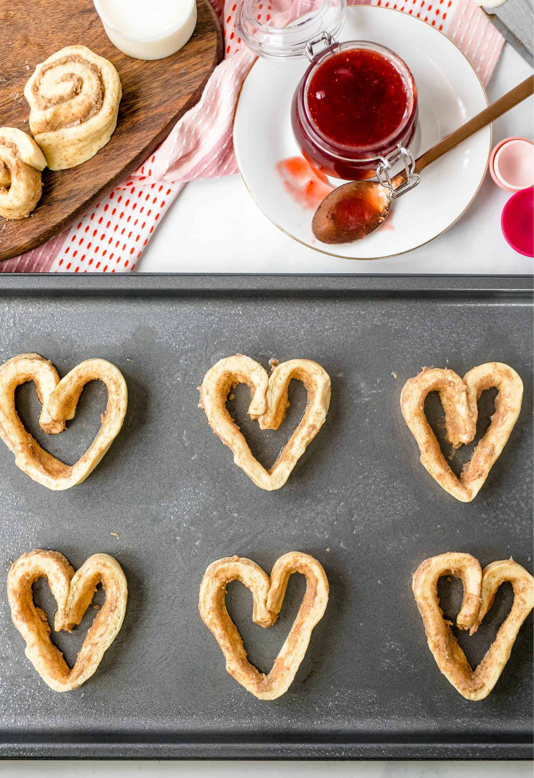 cinnamon roll dough shown shaped into hearts and on a cookie sheet.