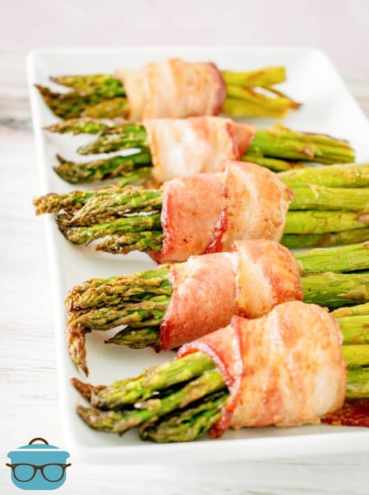 Air Fryer Bacon Wrapped Asparagus laid out on white platter