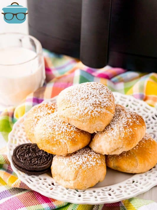 Air Fryer Fried Oreo Recipe stacked on plate topped with powdered sugar with milk next to plate