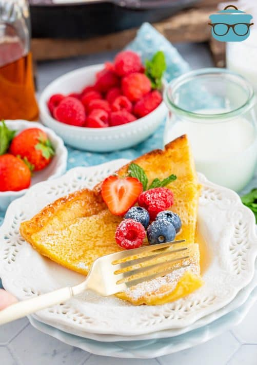Slice of Dutch Baby Pancake on white plate topped with fruit and syrup