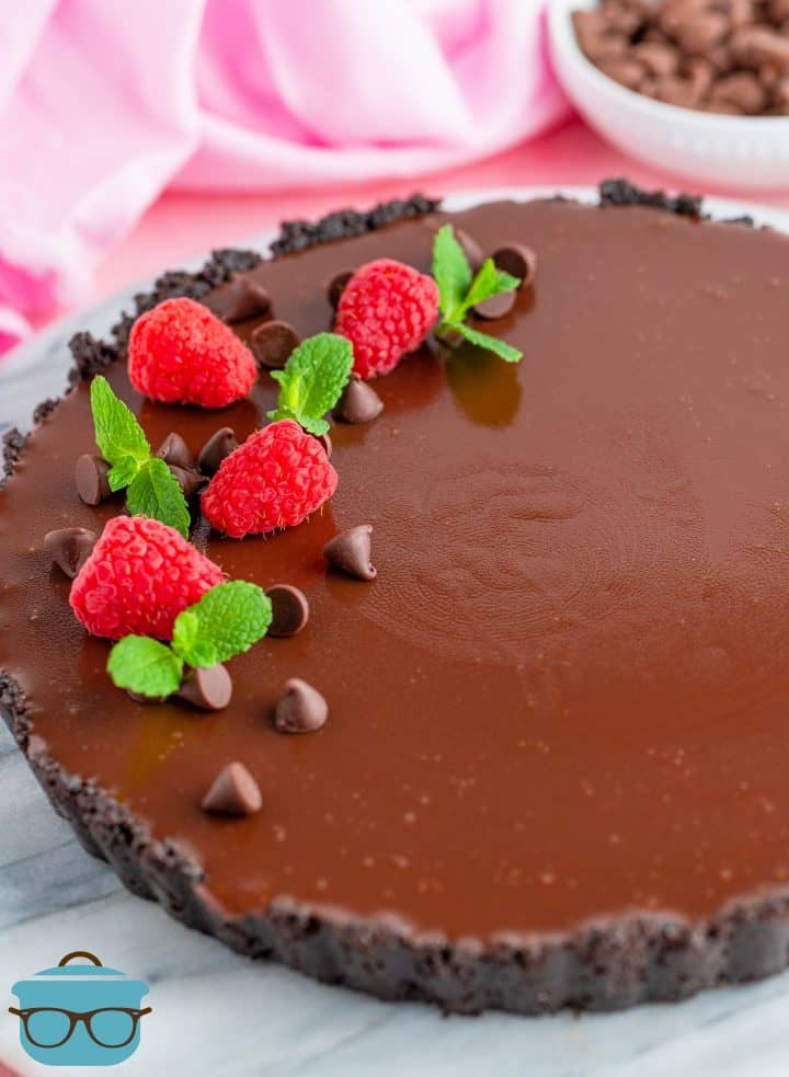 Easy Raspberry Chocolate Tart topped with raspberries, chocolate chips and mint