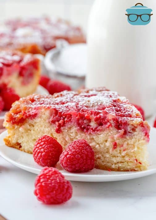 Slice of Raspberry Upside Down Cake on white plate with raspberries