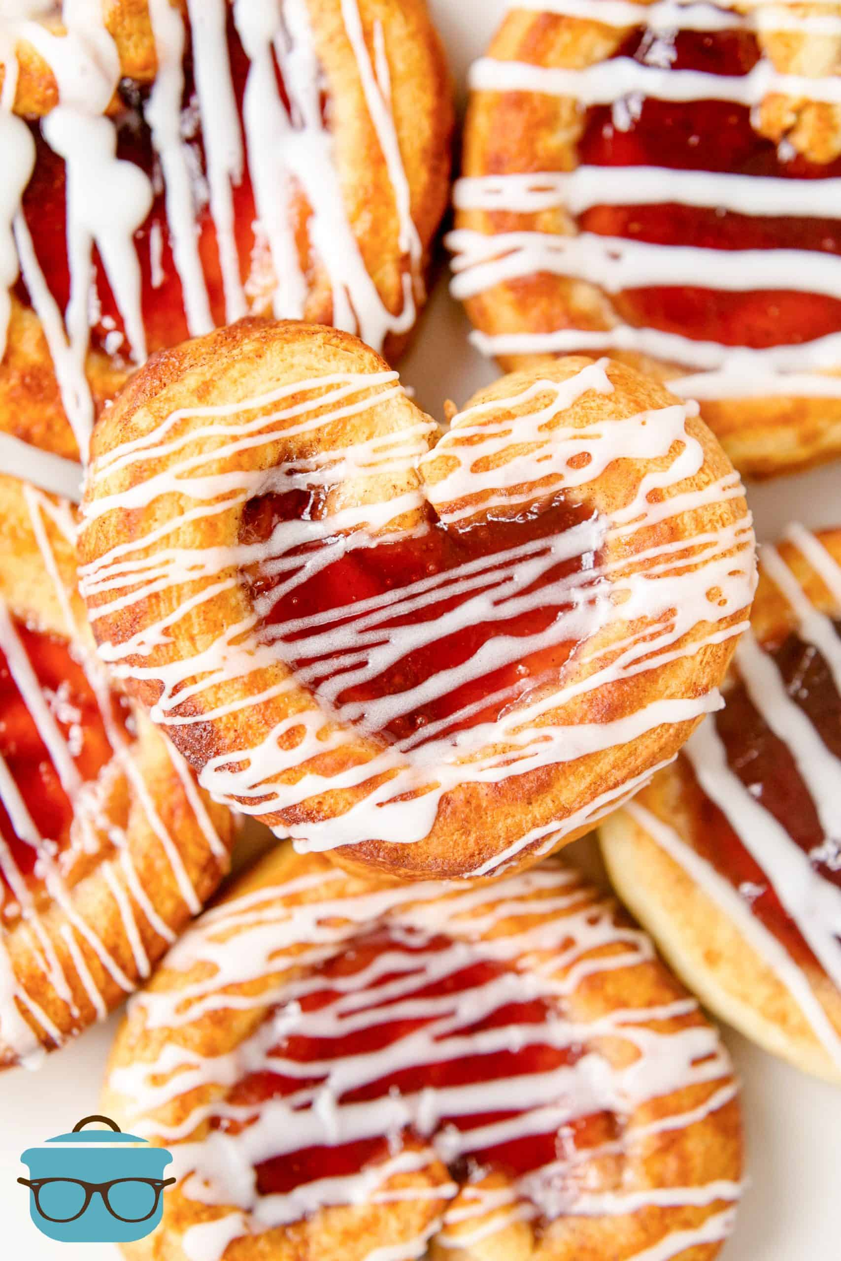 Valentine's Day Cinnamon Rolls Stacked on top of one another and drizzled with icing.