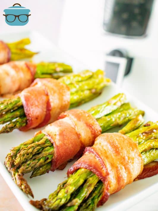 Close up of cooked bacon on Air Fryer Bacon Wrapped Asparagus on white platter