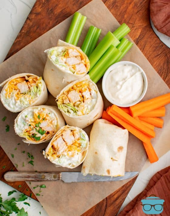 Overhead of cup open Buffalo Chicken Wraps with dipping sauce, celery and carrot sticks