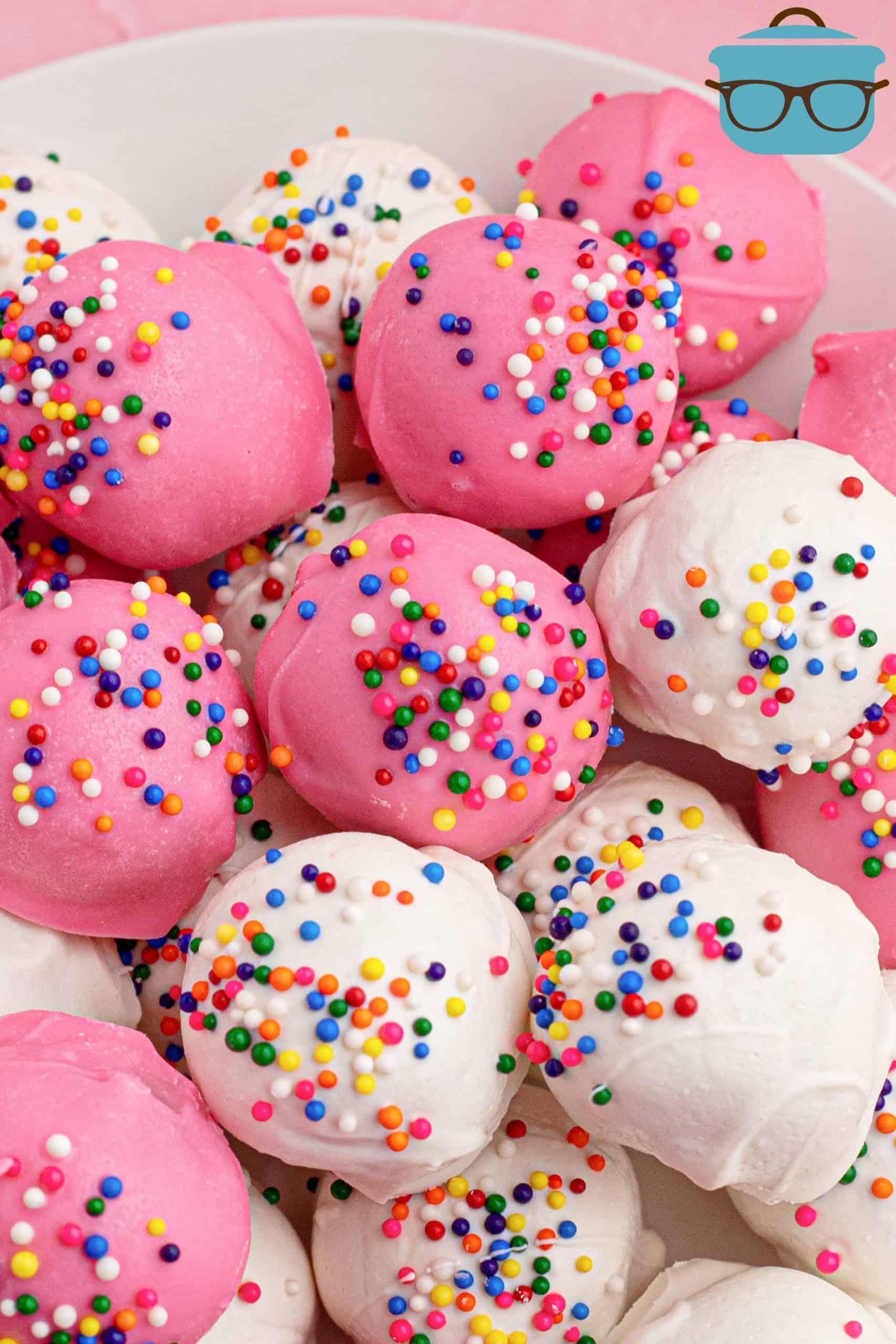 Close up of white and pink coated Circus Animal Cookie Balls in bowl.