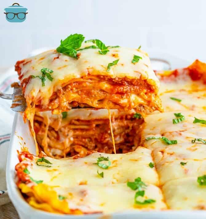 Piece of Homemade Baked Lasagna being lifted out of baking dish