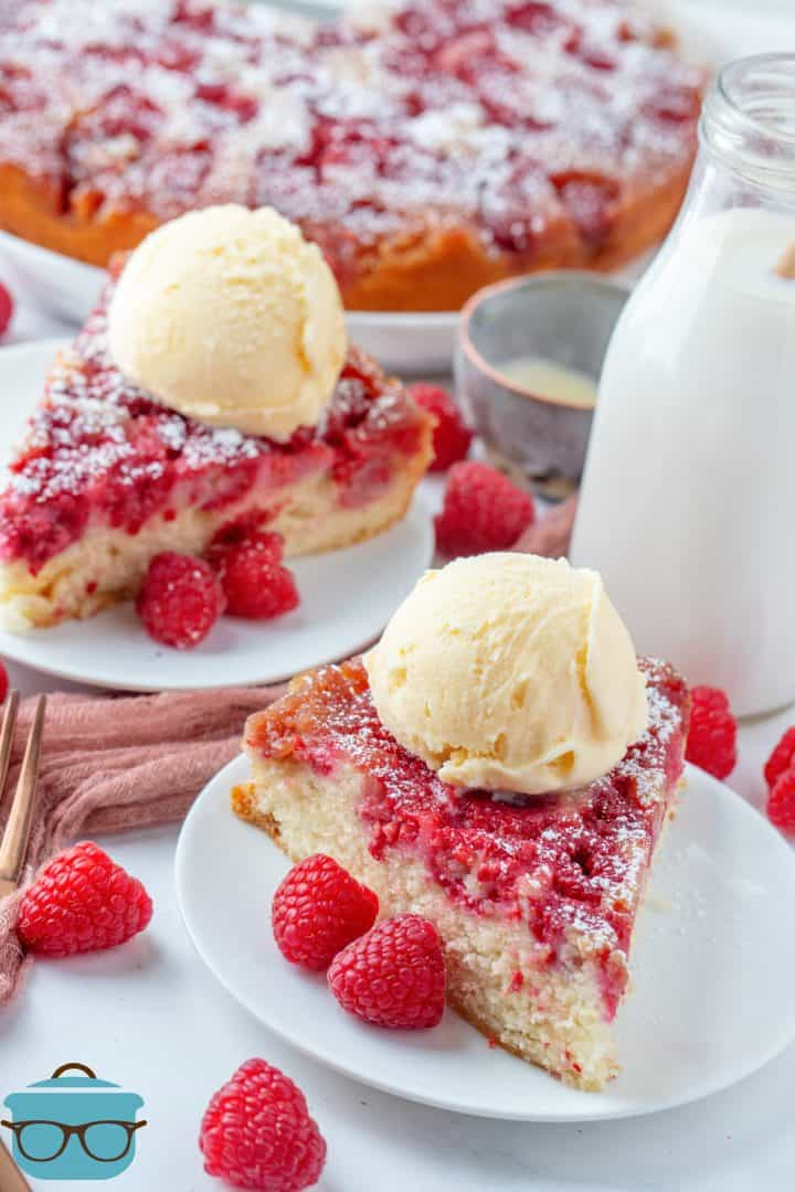 Two slices of Raspberry Upside Down Cake on white plates topped with ice cream