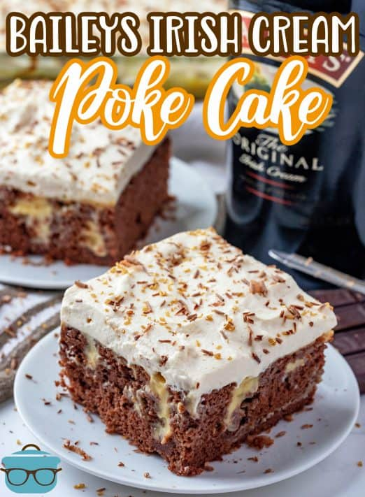 Baileys Irish Cream Poke Cake recipe from The Country Cook, slice of cake shown on a small white plate with a bottle of Baileys Irish cream in the background