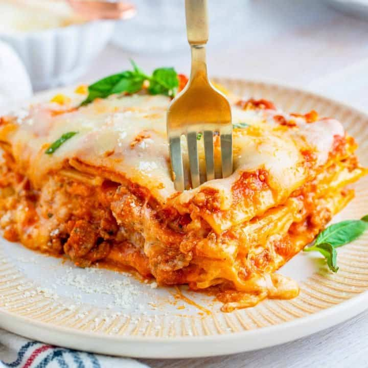 Slice of Homemade Baked Lasagna on plate with fork square image