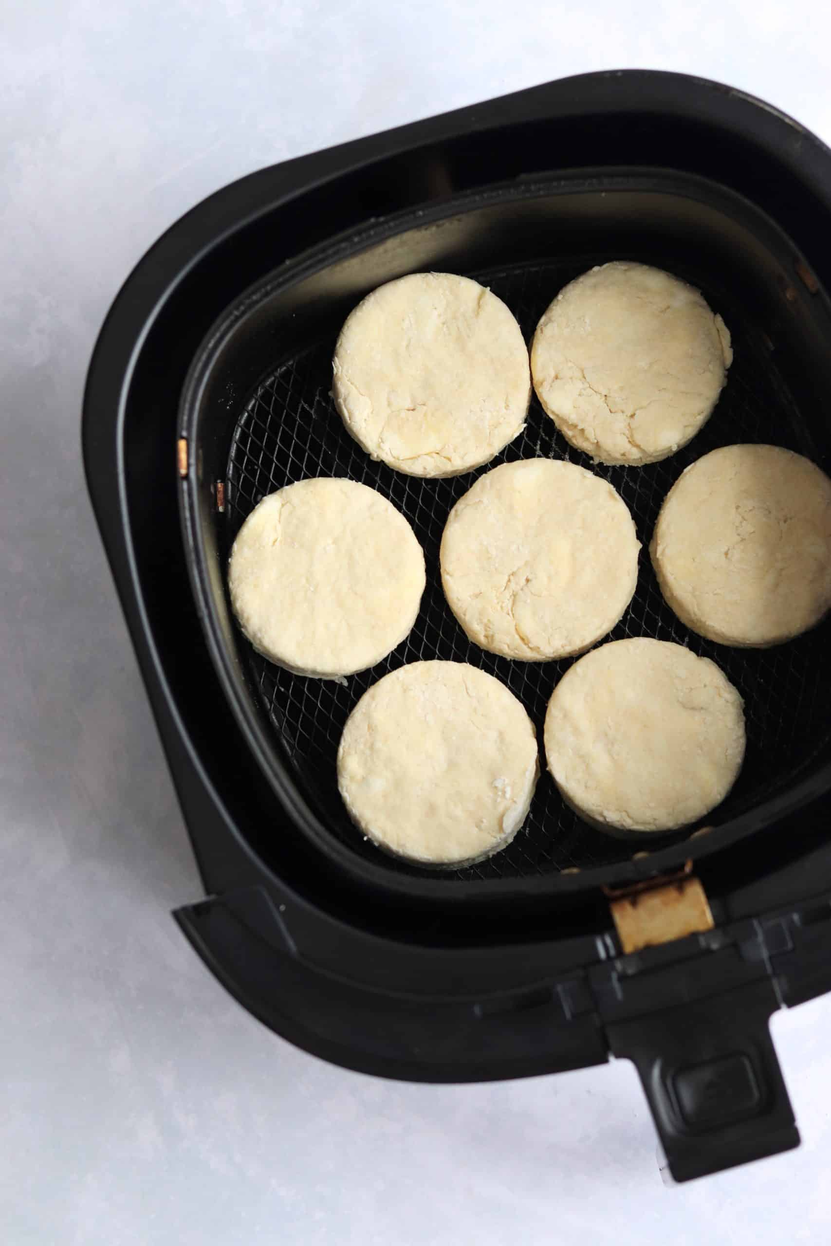 Cut biscuits added to air fryer basket.