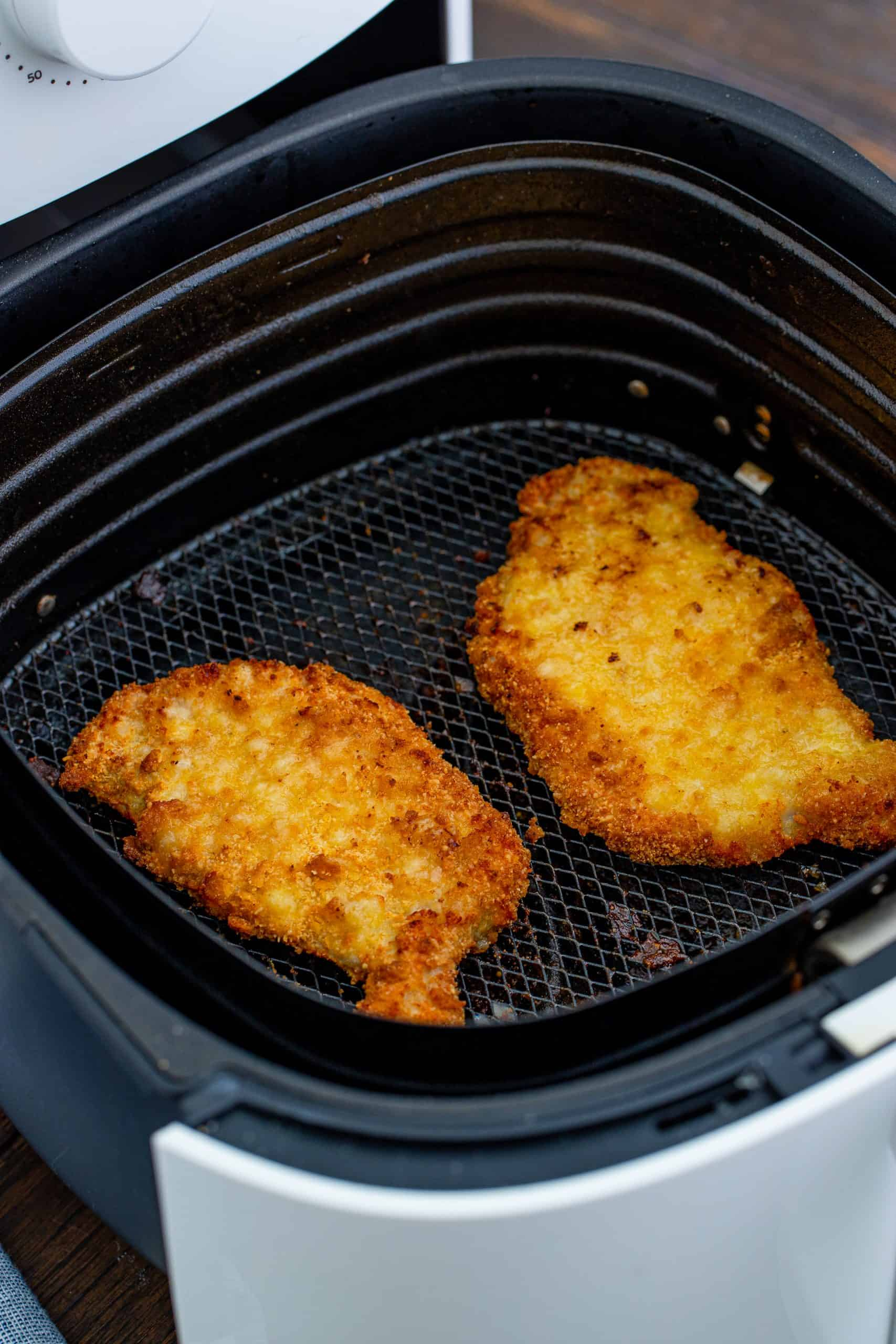 Two Air Fryer Pork Chops shown fully cooked in the air fryer basket.