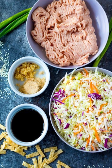 Ingredients needed to make Chicken Egg Roll in a Bowl: garlic ground chicken, coleslaw mix, soy sauce, brown sugar, pepper, green onions, sesame seeds, wonton strips