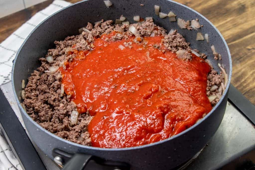 spaghetti sauce added to cooked ground beef in a skillet