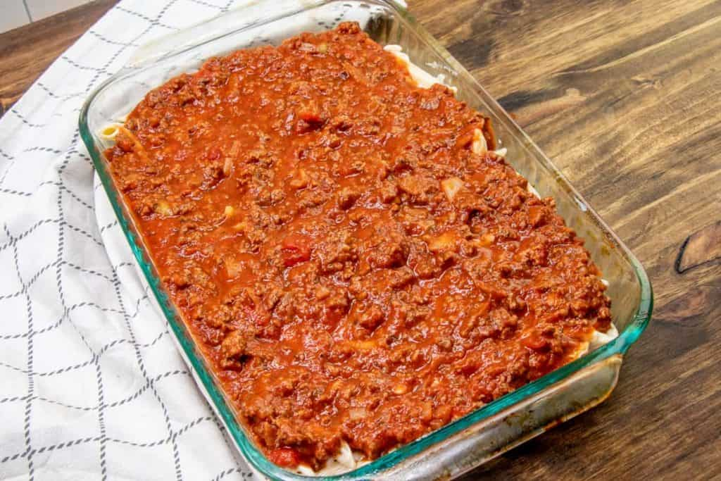 ground beef spaghetti sauce evenly spread on top of pasta in casserole dish