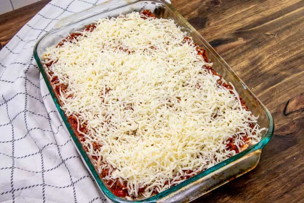 shredded mozzarella cheese sprinkled on top of spaghetti sauce and creamy pasta