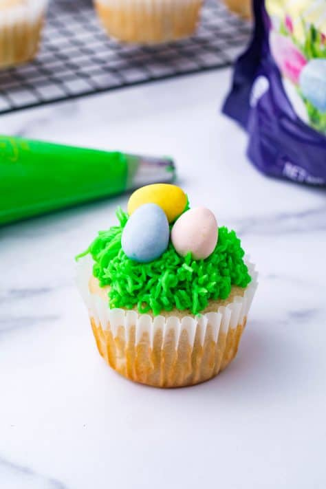 Finished Easter Egg Cupcake with piping bag behind it