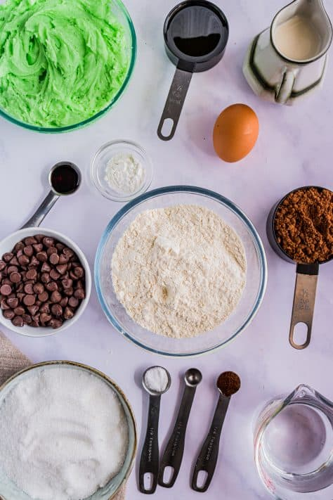 Ingredients needed to make Mint Chocolate Chip Cupcakes: all-purpose flour, cocoa powder ,granulated sugar, baking powder, espresso powder, salt, oil, egg, vanilla extract, mint extract, buttermilk, water, chocolate chips, butter, powdered sugar, heavy cream, green gel coloring