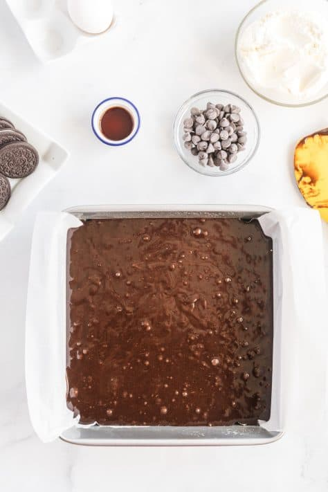 Brownie mix poured into lined baking pan