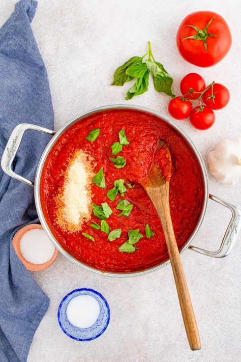 Overhead of pan with cooked pizza sauce with basil leaves and parmesan added