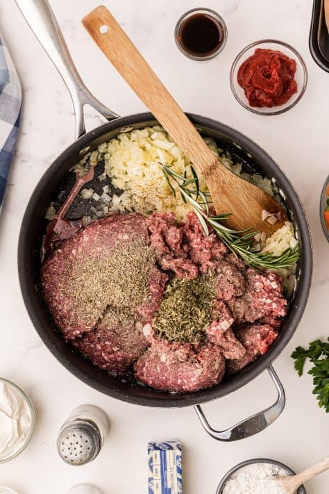 Ground meat and herbs added to onions