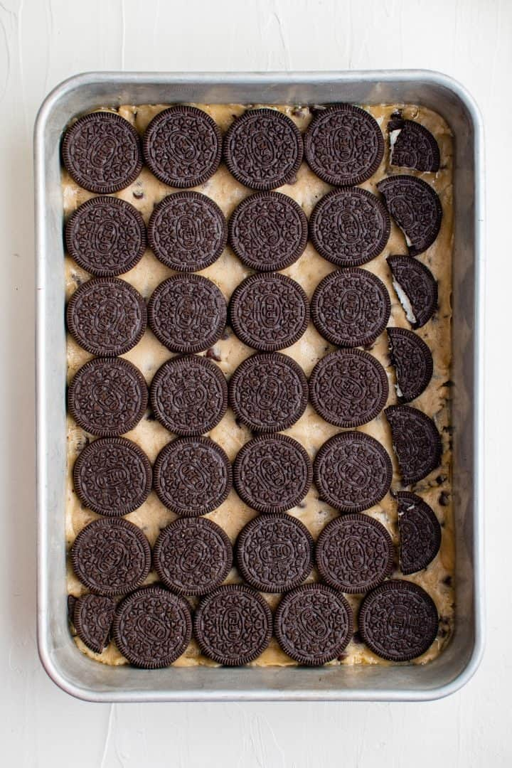 Oreos laid out in a single layer on top of cookie dough.