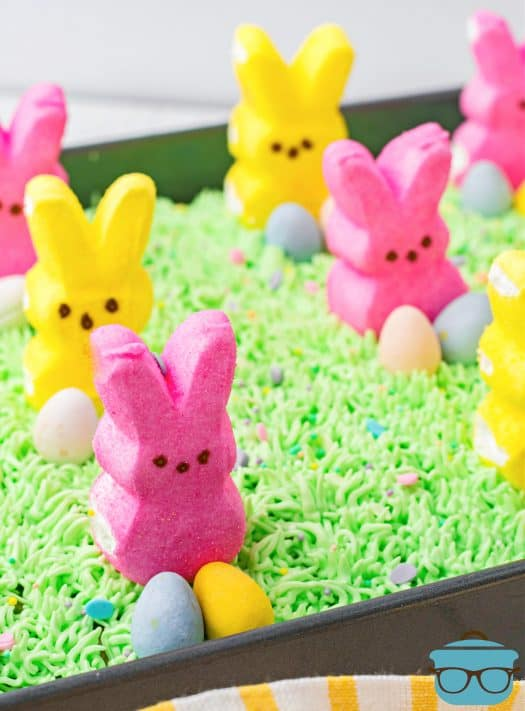 Finished Easter Bunny Poke Cake topped with bunny peeps and mini Cadbury eggs.
