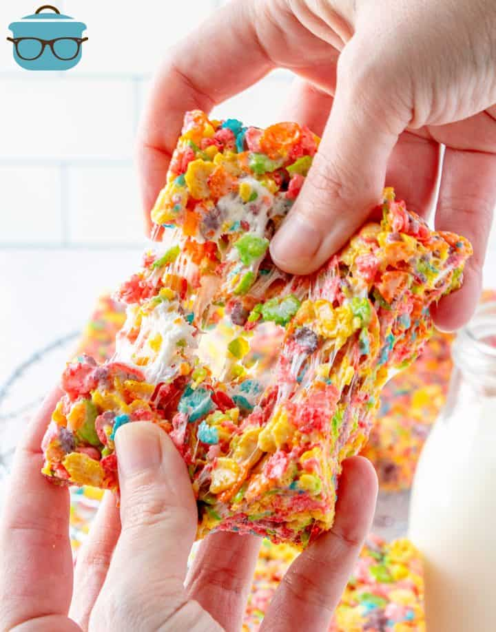 Hand pulling apart one Fruity Pebbles Treat