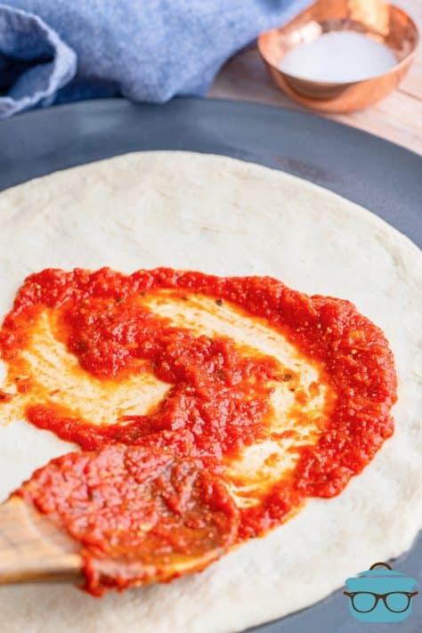 Homemade Pizza Sauce being spread on pizza dough