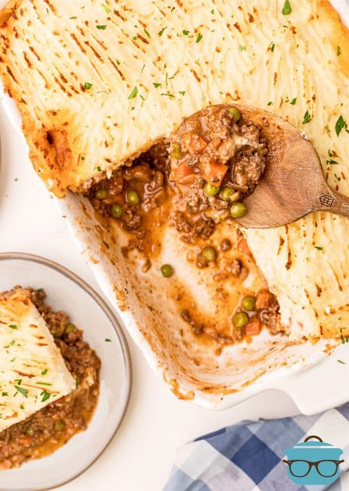 Overhead photo of slice of Shepherd's Pie on plate with some removed from casserole dish