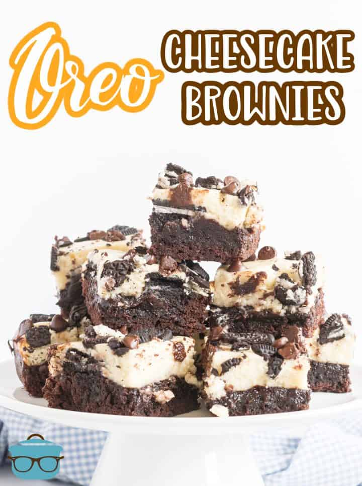 Stacked Oreo Cheesecake Brownies on a white cake stand.