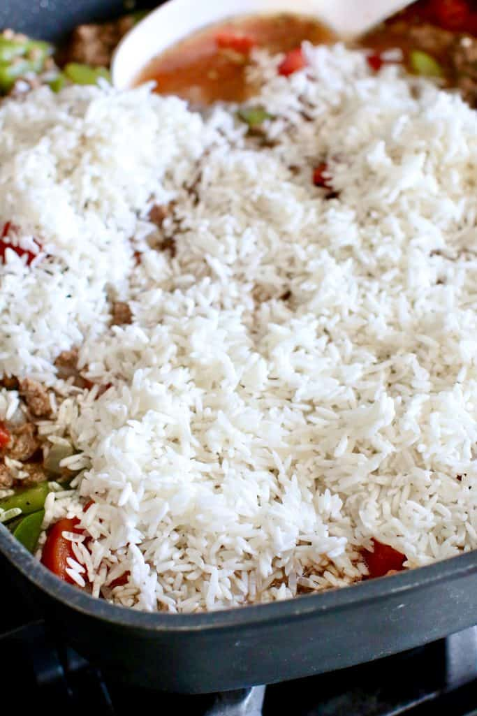 uncooked rice added to large skillet with other stuffed pepper casserole ingredients