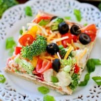 slice of vegetable pizza shown on a small white plate