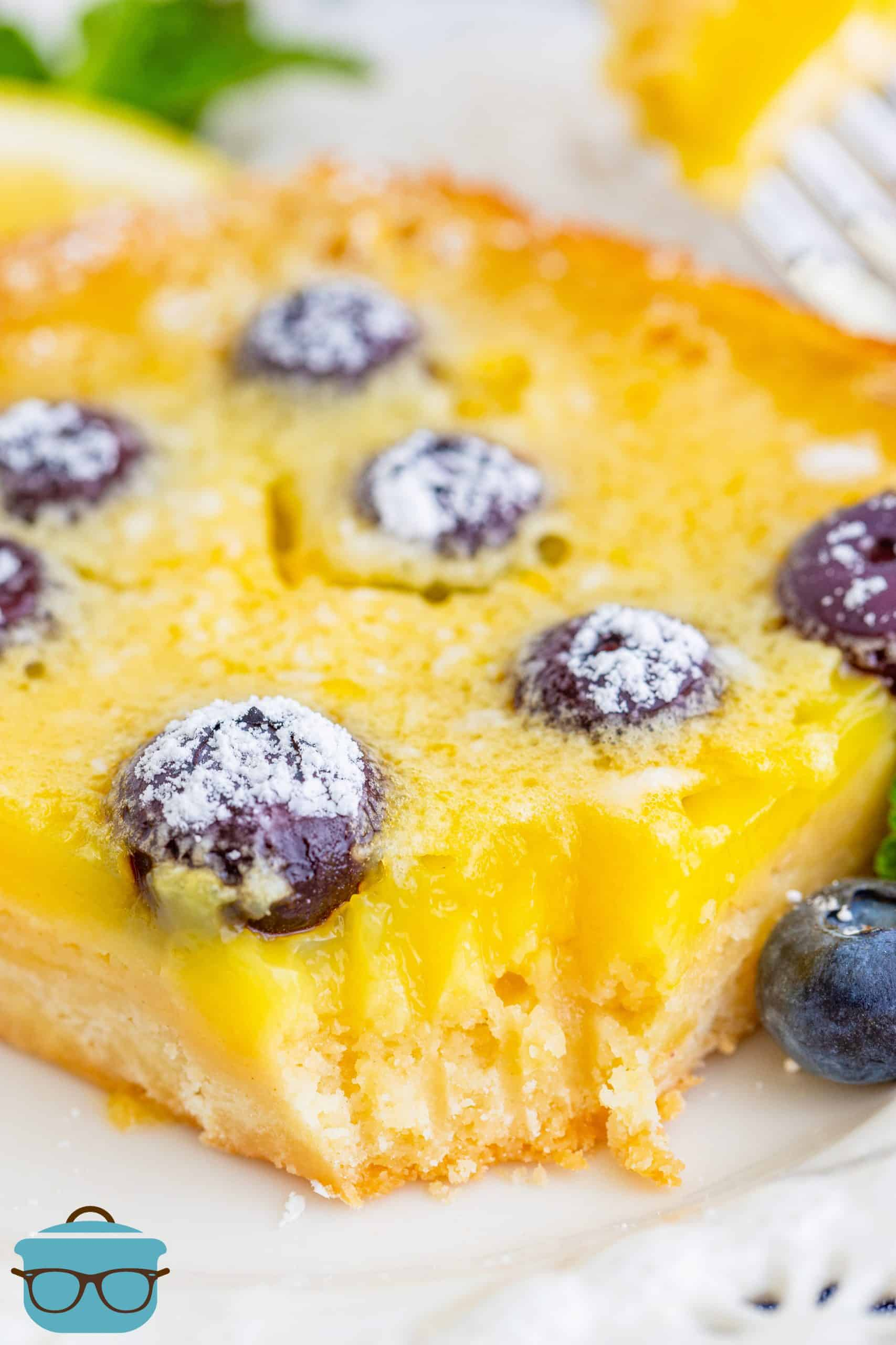 Blueberry Lemon Bar on white plate close up with bite taken out of it.