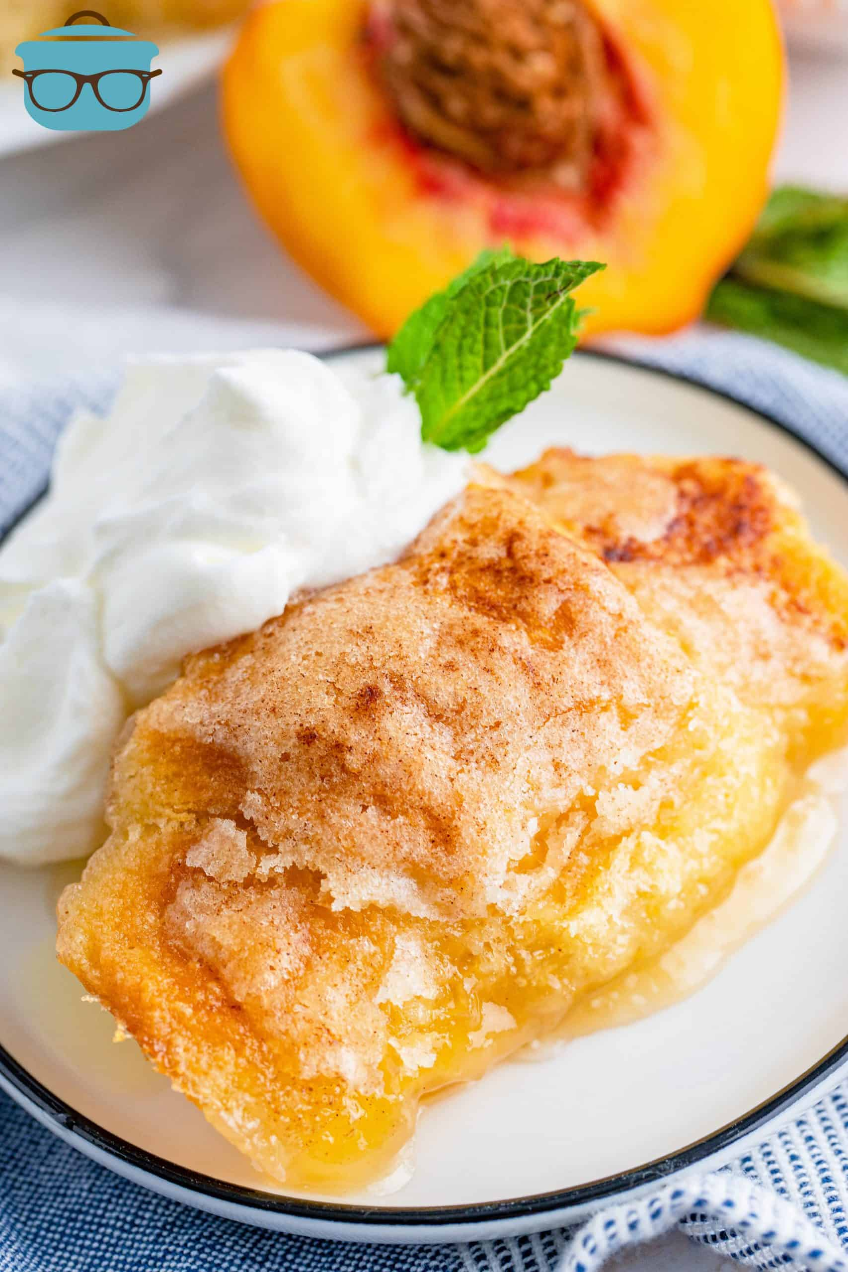One Peach Dumpling on plate with whipped cream.