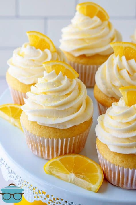 Homemade Lemon Cupcakes on cake stand topped with lemon slices