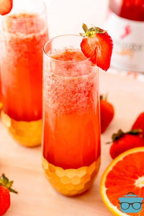 Close up of Strawberry Mimosas in two glasses garnished with strawberries