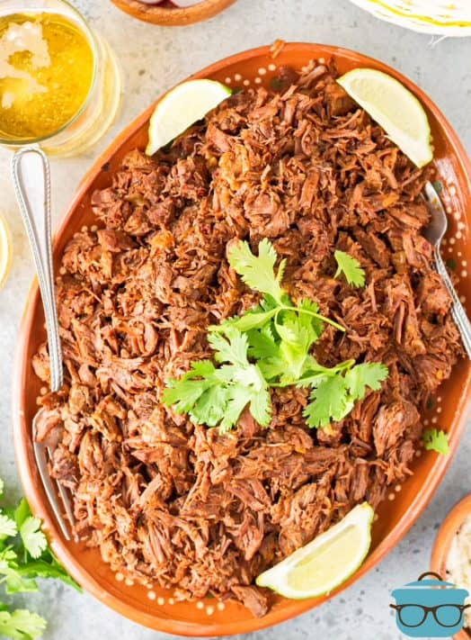 Overhead of Instant Pot Barbacoa on platter with cilantro and lime