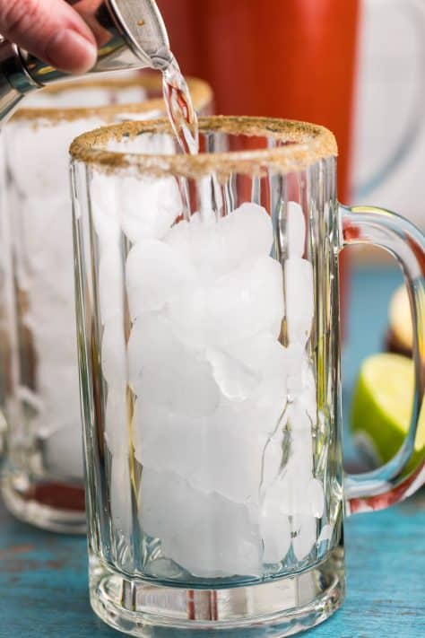 Glasses with ice and vodka being poured into them