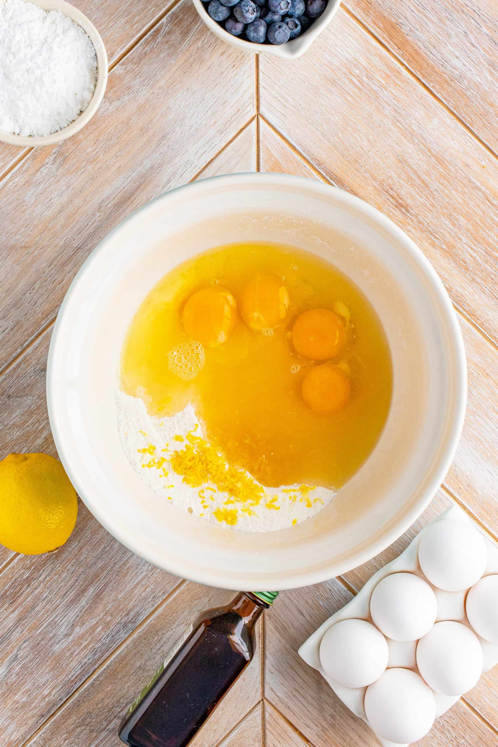 Eggs and lemon zest added to flour and sugar mixture in white bowl.