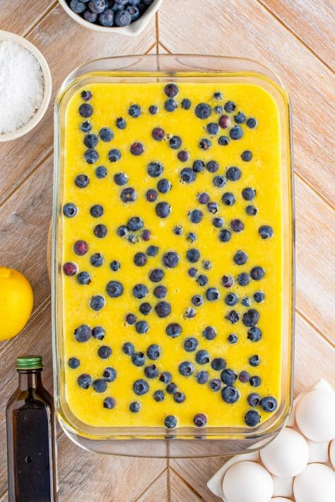 Blueberries sprinkled over filling mixture in baking pan.