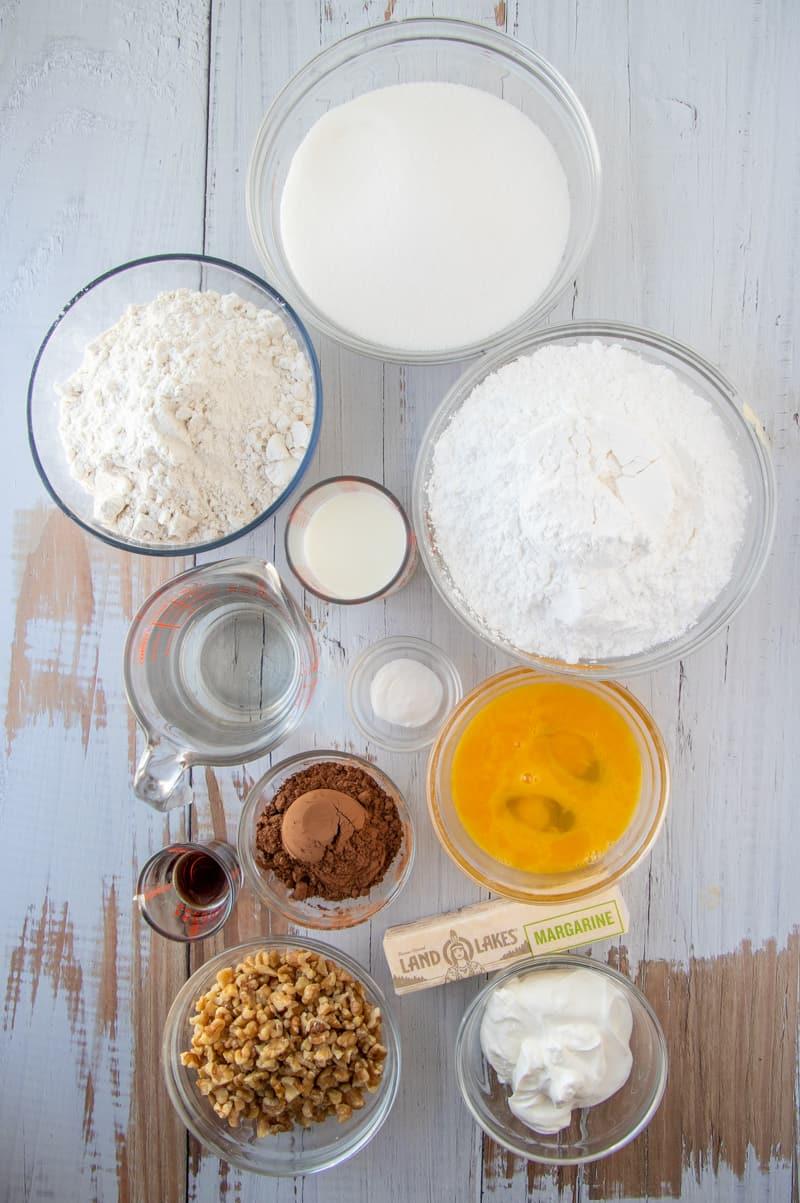 Ingredients needed: margarine, water, cocoa powder, all-purpose flour, eggs, baking soda, granulated sugar, sour cream, milk, walnuts, powdered sugar and vanilla extract.