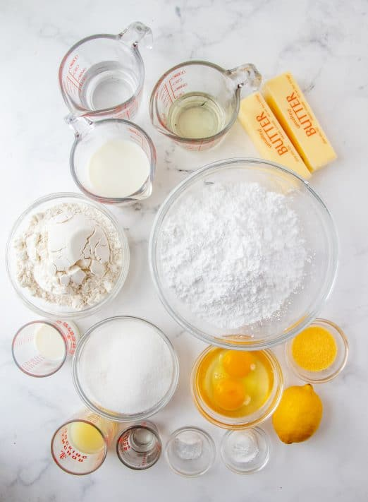 Ingredients needed all-purpose flour, granulated sugar, baking powder, baking soda, lemon extract, lemon zest, eggs, milk, water, vegetable oil, butter, lemon juice, powdered sugar and heavy cream